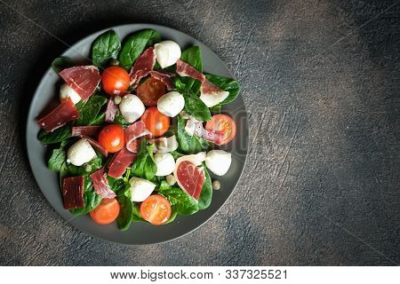 Salad With Prosciutto, Mozzarella, Cherry Tomatoes, Capers And Spinach On A Dark Plate On A Dark Bac