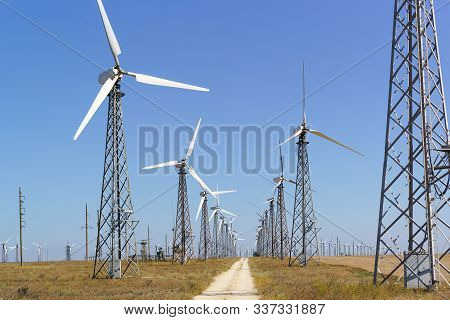Huge Blades Of A Wind Generator On A High Mast In The Crimean Steppe . Wind Is An Inexhaustible Sour