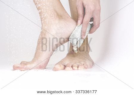 Woman Using Pumice To Exfoliate The Dead Skin From