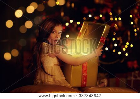 Magic for Christmas. Happy excited little girl opens a box with gifts and surprises. Beautiful Christmas tree in the background.