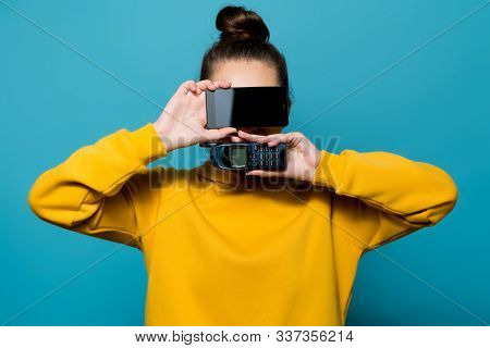 Portrait Of A Young Woman, She Covers Her Face With Old And New Model Cell Phones