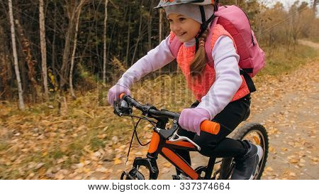 One Caucasian Children Rides Bike Road In Autumn Park. Little Girl Riding Black Orange Cycle In Fore