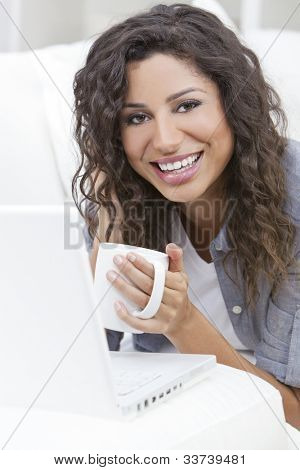 Beautiful young Latina Hispanic woman smiling, relaxing and drinking a cup of coffee or tea using laptop computer