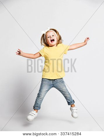 Active Cheerful Happy Kid Baby Girl Blonde In Yellow T-shirt, Blue Jeans And Sneakers Is Jumping Hig