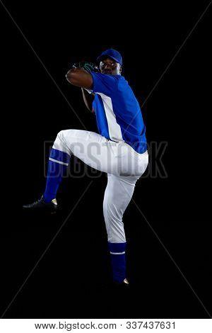 Front view of an African American male baseball player, a pitcher wearing a team uniform, baseball cap and a mitt, preparing to pitch a baseball. Vertical shot