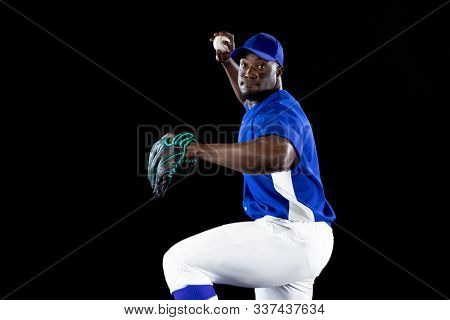 Front view of an African American male baseball player, a pitcher wearing a team uniform, baseball cap and a mitt, preparing to throw a pitch