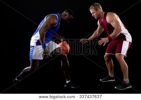 Side view of an African American male basketball player wearing team colours dribbling the ball watched closely by a Caucasian male player on the opposing team defending his basket