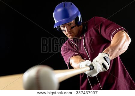 Front view close up of a Caucasian male baseball player, a hitter wearing a team uniform and a helmet, swinging a baseball bat and hitting a baseball