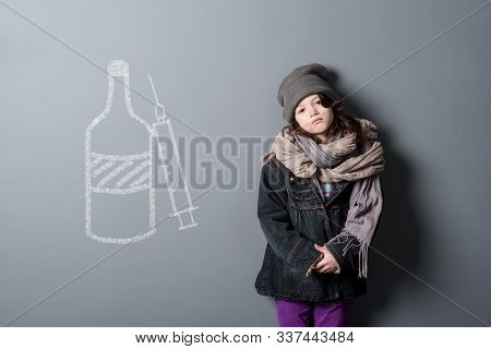 Neglected Kid In Shabby Clothes On The Grey Background