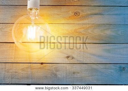 Hanging incandescent lamp on wooden wall. Edison type bulb. Space for text. The deck of an old ship.