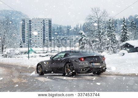 Kuffstein, Germany - Janyary 12th, 2019: Black Modern Ferrari Ff Supercar Driving Along Dirty Mud Sl