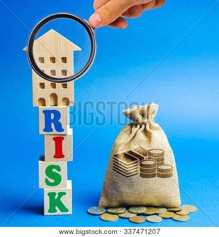 Wooden Blocks With The Word Risk And A Miniature House With A Money Bag. Real Estate Investment Risk
