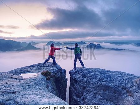 Hikers Or Climbers In Mountains. Couple Hold The Light  High Above Danger Gulch Between Rocks. Night