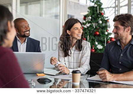 Group of happy business people in meeting during christmas holiday. Smiling businessman and businesswoman discussing new project strategy during xmas time. Successful multiethnic business partners.