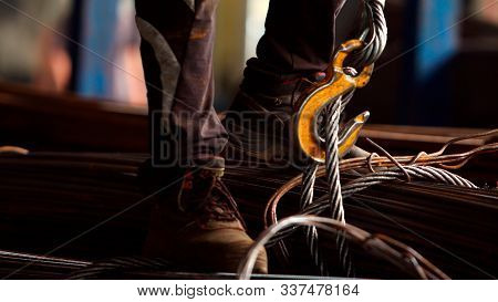 Worker loading rebar and hanging the load on the crane's chains in metalworking factory. Concept for industrial worker, manual work and manufacturing. Close up. Selective focus. poster