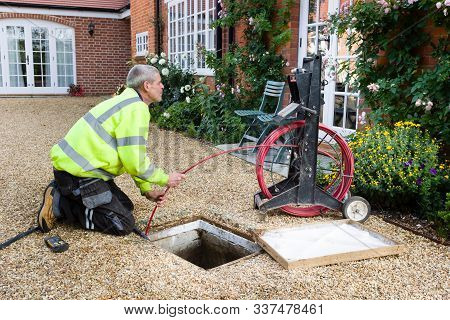 Buckingham, Uk - October 16, 2019. A Professional Drain Cleaning Engineer Inspects A Blocked Househo