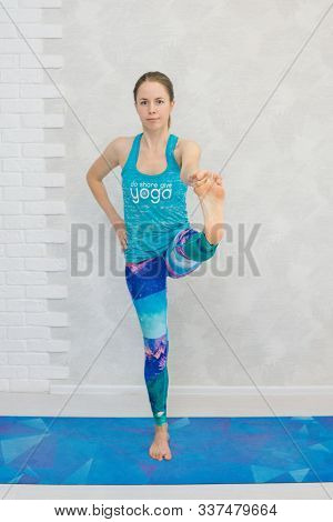 Portrait Of Beautiful Young Woman Practicing Yoga Indoor. Girl In Blue Sportswear Practice Utthita H