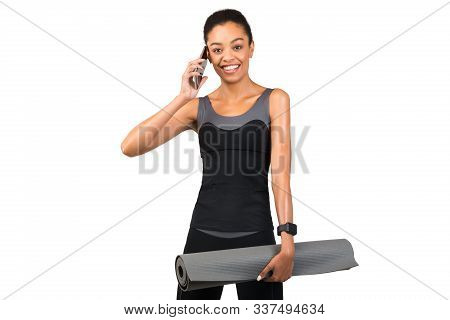 African American Woman In Fitwear Talking On Cellphone Holding Yoga Mat Standing Over White Studio B
