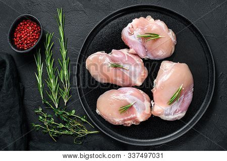 Raw Chicken Thigh Fillet Without Skin. Farm Poultry Meat. Black Background. Top View