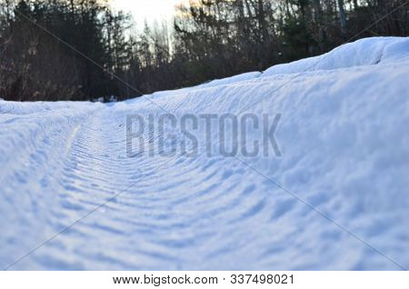 Wheel Tread On White Snow. The Trail From The Tread Of Truck Wheel In The Snowу Road In Winter Time.
