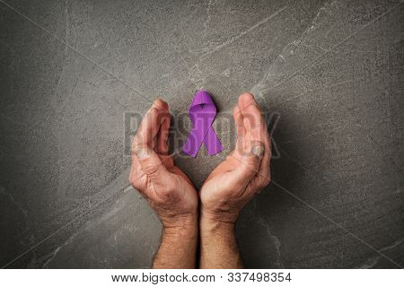 Hands Holding Purple Ribbons Top View On Dark Gray Background. Alzheimers Disease, Epilepsy, Fibromy