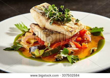 Pollock fish fillet with vegetables on white plate. Gourmet delicious food. Baked fish piece with sweet and sour sauce and herbs side view. Seafood with steamed veggies meal on black table