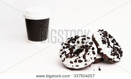 Delicious Fresh Donuts Black And White Color With White Icing And Chocolate Chips With Paper Glass O