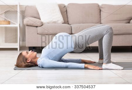 Pregnancy Fitness. Focused Young Pregnant Woman Doing Prenatal Shoulder Bridge Exercise. Copy Space