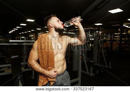 Sports Handsome Man Drinking Water After The Raining In The Empty Gym.