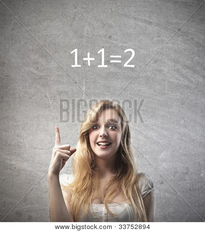 Smiling young woman finding the solution to the easy calculation over her head