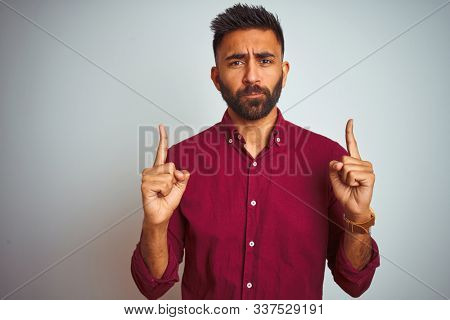 Young indian man wearing red elegant shirt standing over isolated grey background Pointing up looking sad and upset, indicating direction with fingers, unhappy and depressed.