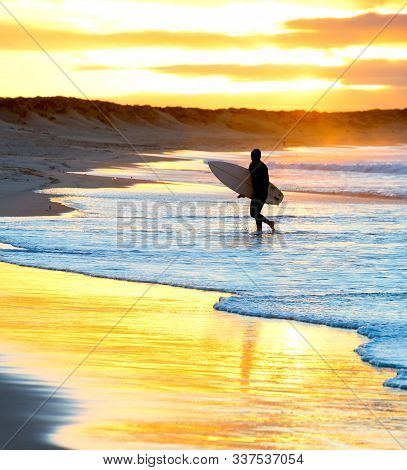 Silhouette Of Surfer Walking By The Beach With Surfboard At Sunset. Baleal, Portugal