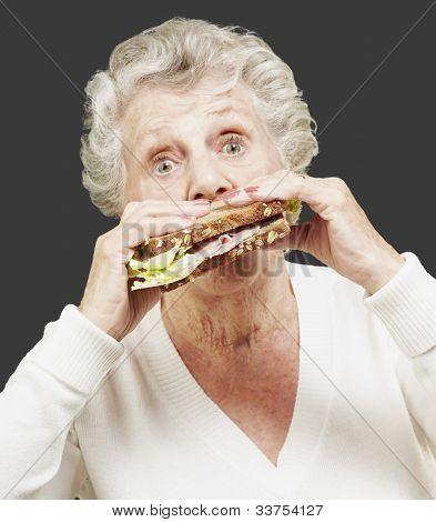 senior woman eating a healthy sandwich against a black background