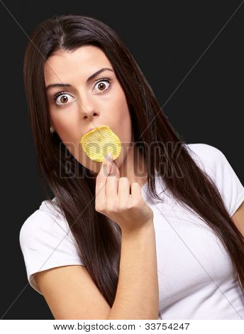 portrait of a young woman holding potato chip on her mouth over a black background