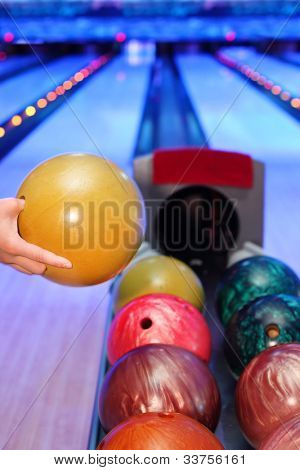 Hand of man, which takes yellow ball for throw in bowling club