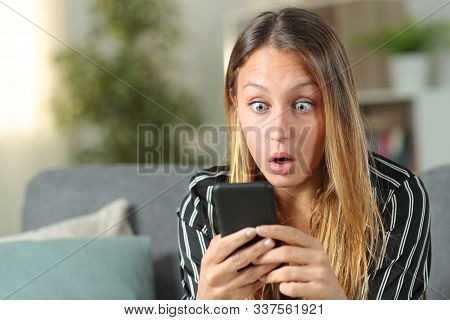 Surprised Woman Finding Amazing Content On Mobile Phone Sitting On A Couch In The Living Room At Hom