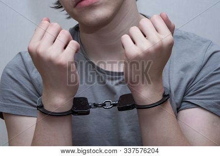 A Handcuffed Teenager Sits On A Grey Background. Juvenile Delinquent, Criminal Liability Of Minors.
