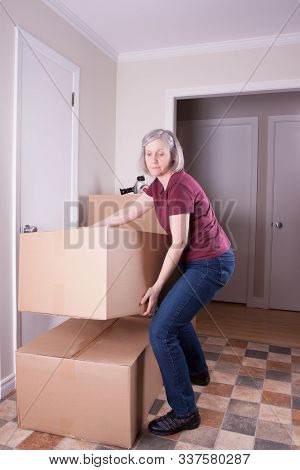 Mature Grey Haired Woman Prepares To Move To Another House Stacks Big Brown Boxes