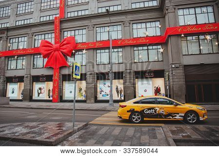 12 04 2019, Moscow: A Yellow Gett Taxi Car Rides Past The Tsum, Decorated With A Red Bow For The New
