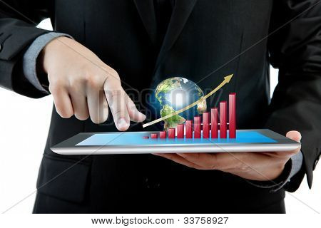 Business man holding the modern digital tablet pc with success growth chart and earth (Elements of this image furnished by NASA)