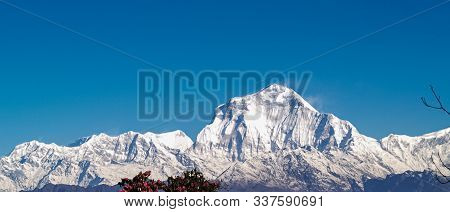 Mountain Landscape Panorama. Majestic Mountain Peaks Covered With Snow Against A Bright Blue Sky.