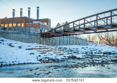 footbridge over Cache la Poudre River at new whitewater park in downtown of Fort Collins Colorado with Powerhouse Energy Campus of Colorado State University in background, winter sunset scenery