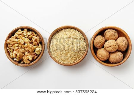 Whole walnuts, walnut kernel and ground walnuts in wooden bowls on white background.