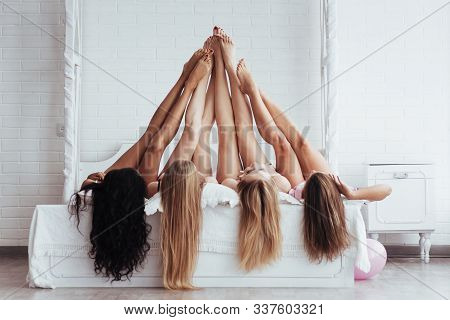 Touching Each Other. Four Young Women With Good Body Shape Lying On The Bed With Their Legs Up.
