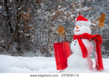 The Snowman Is Wearing A Fur Hat And Scarf. Winter Scene With Snowman On White Snow Background. Wint