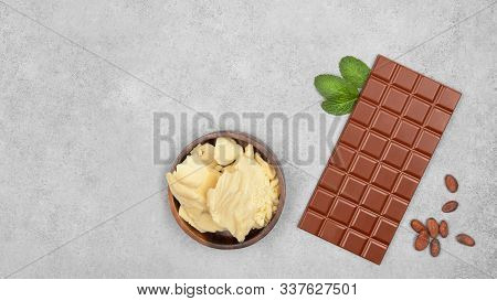 Bar Of Milk Chocolate, Cocoa Butter, Mint And Cocoa Beans On Gray Stone Background. Top View With Co