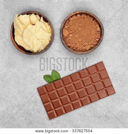 Bar Of Milk Chocolate, Cocoa Powder, Cocoa Butter And Mint On Gray Stone Background. Top View