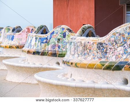 Barcelona, Spain - August 2019: Multicolour Mosaic Pattern On Benches, Medium View. Park Guell In Ba