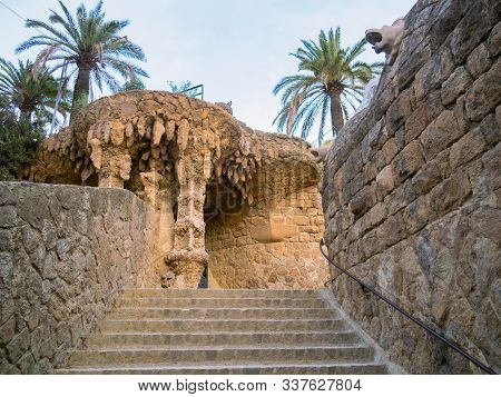 Barcelona, Spain - August 2019: Upstairs Between Brickwalls, Stalactites, Green Palm Trees, Medium V
