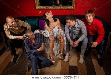 Crazy wedding party in night club. Friends of groom make a drunkard of bride